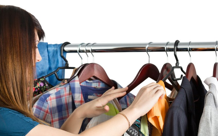 41331133 - beautiful young woman near rack with clothes choosing what to take. nothing to wear, shopping and sale  concept
