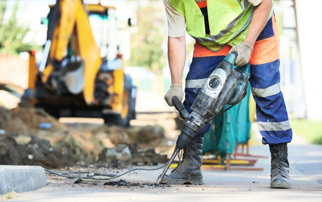 35065563 - builder worker with pneumatic hammer drill equipment breaking asphalt at road construction site