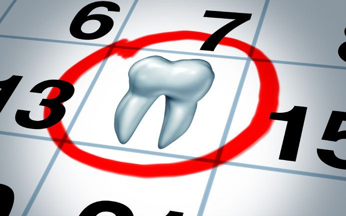 24809456 - dentist appointment and dental check up health care concept as a month calendar with a tooth circled and highlighted as a reminder metaphor for a dentist visit time at a clinic for scheduled oral care