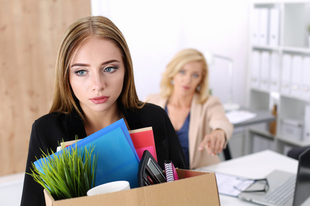 45107583 - boss dismissing an employee. dejected fired office worker carrying a box full of belongings.