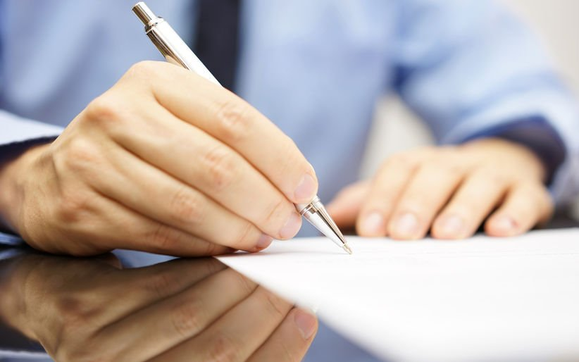 34744134 - businessman is writing a letter or signing a agreement