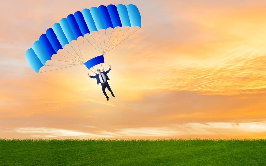 91077735 - young businessman falling on parachute in business concept
