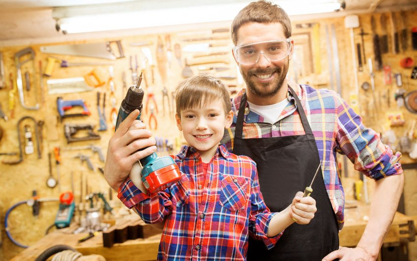 64678407 - family, carpentry, woodwork and people concept - happy father and little son with drill and screwdriver working at workshop