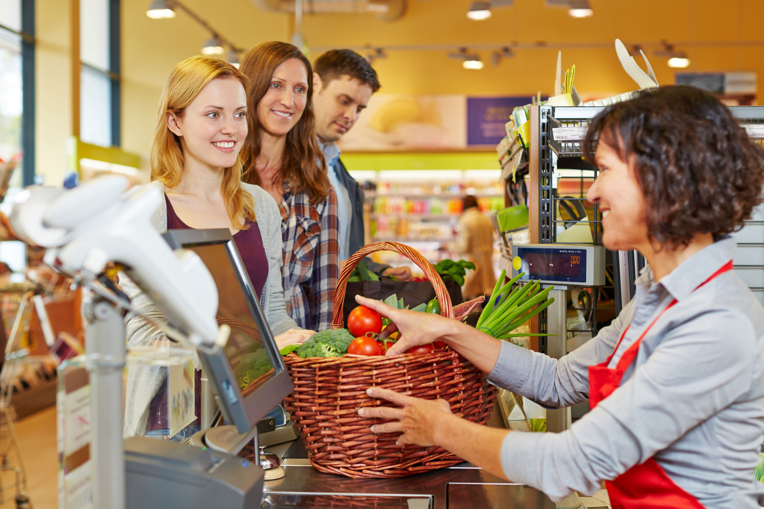 29682877 - young woman paying basket of groceries at supermarket checkout